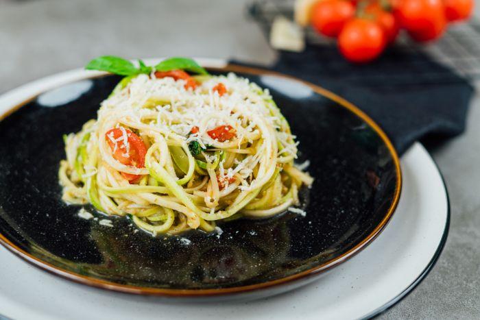 spaghetti de légumes aux courgettes à la sauce tomate, basilic et pesto avec du parmesan râpé