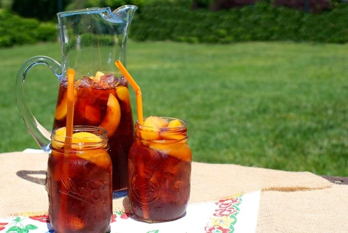 dans quel contenant conserver un thé glacé, idée comment servir un thé glacé avec tranches de pêches et glaçons