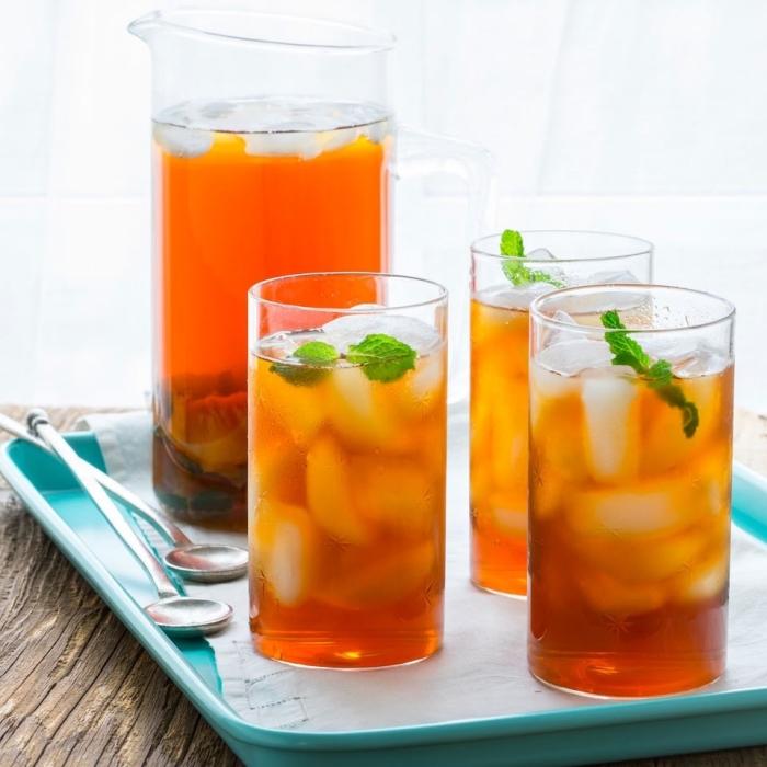 boisson saine au thé vert refroidi avec tranches de pêche et miel, comment servir un thé glacé avec feuilles de menthe