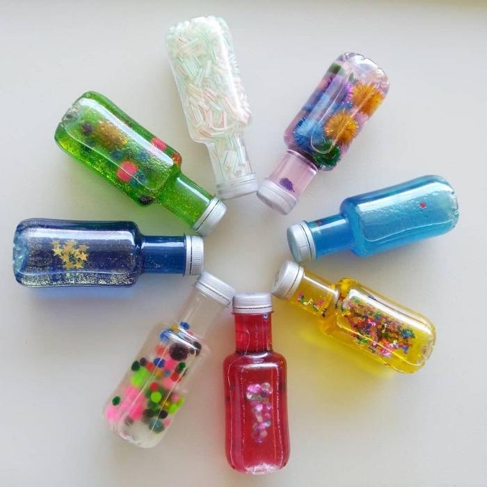 exemples de bouteilles sensorielles DIY, modèle bouteille en verre remplie d'eau colorée et de paillette, idée jouet bébé diy