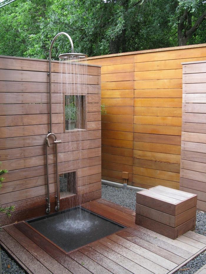 exemple de douche de jardin en inox et à effet pluie avec receveur béton, modèle salle d'eau extérieure en bois