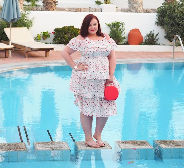 modele de robe pour femme ronde fleurie à volant mi longue avec des bretelles tombantes, sac à main corail