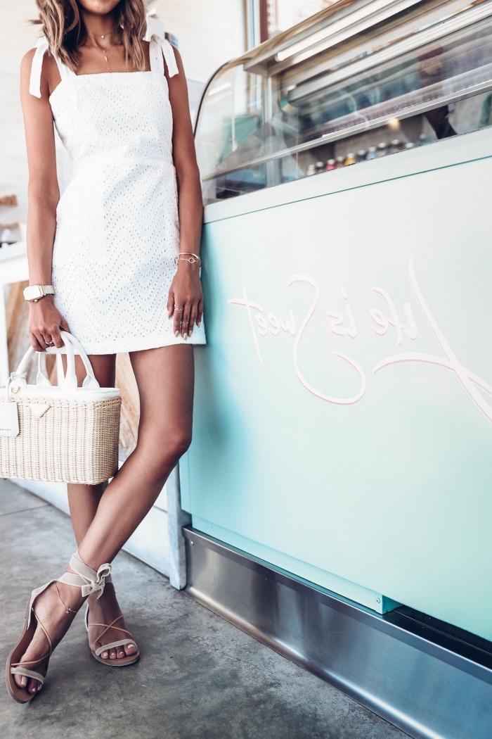 idée comment porter une robe blanche courte avec sandales plates, modèle de sac à main en paille avec poignées blanches
