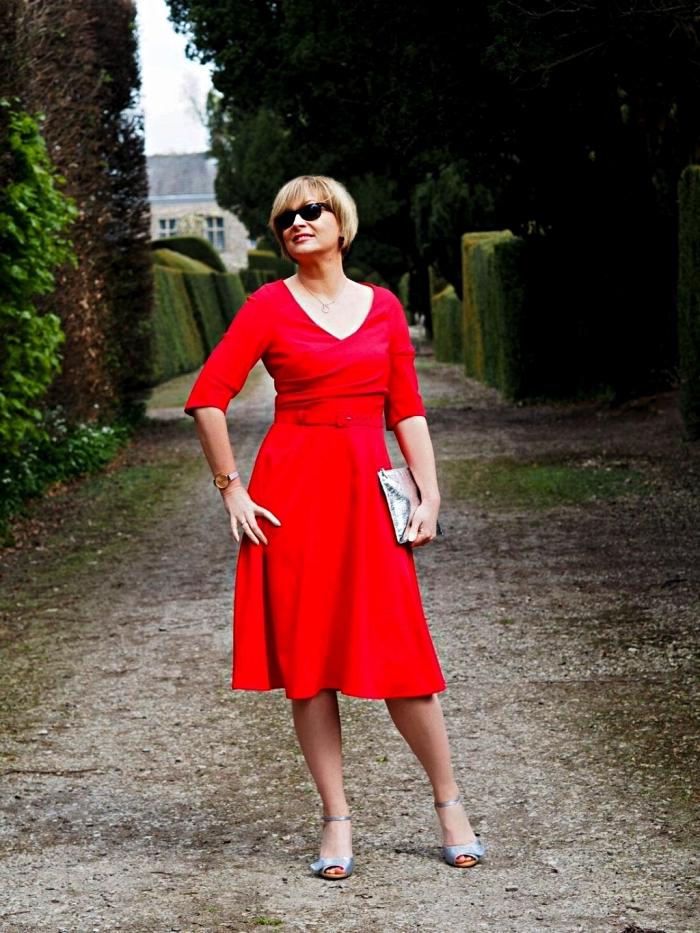 robe de cocktail rouge avec taille ajustée assortie avec des sandales métalliques et une pochette argent, idée de tenue mariage femme 50 ans