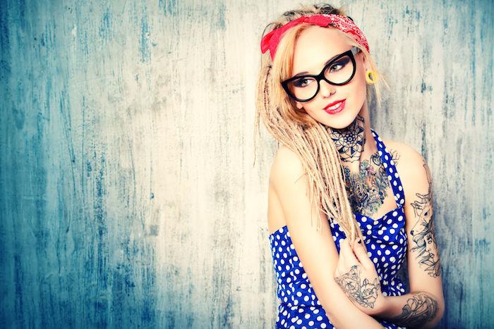 fille rétro, robe bleue pointillée, cheveux en fines tresses, bandana cheveux, plusieurs tatouages