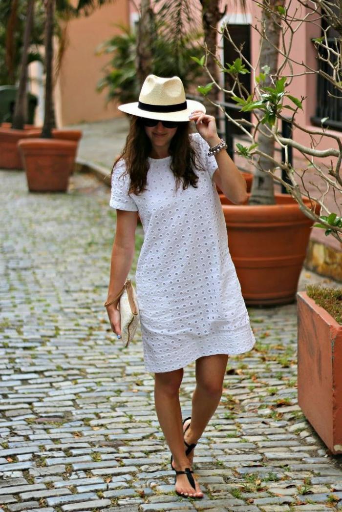 robe tunique blanche, chapeau fédora beige, sac à main beige, sandales noires, arbres plantés en pots