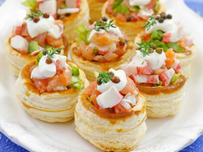 rouleaux de pâtes, saumon fumé, caperses, radis, fromage, assiette blanche, table bleue, apéritif léger