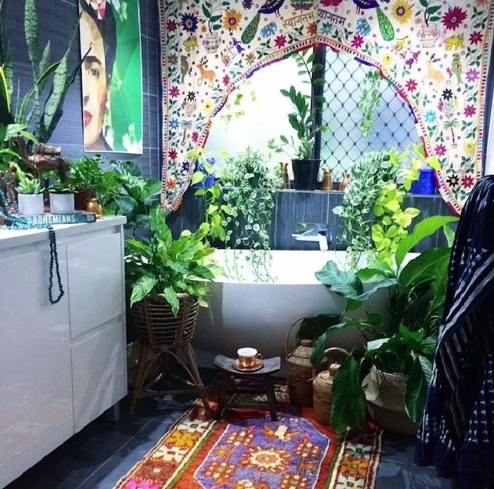 dece murale cadre frida khalo, tapis oriental sur sol carrelage gris, meuble salle de bain blanc, plusieurs végétaux autour d une baignoire, panneau textile imprimé oriental
