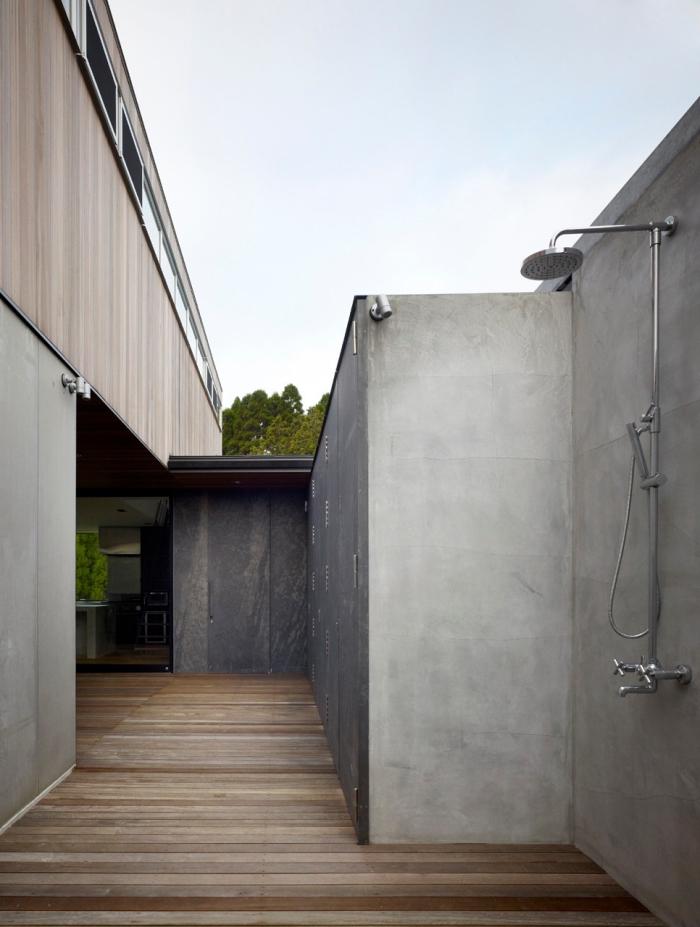 deco exterieur maison, modèle de douche inox installée sur un mur extérieur en béton avec sol en planches bois