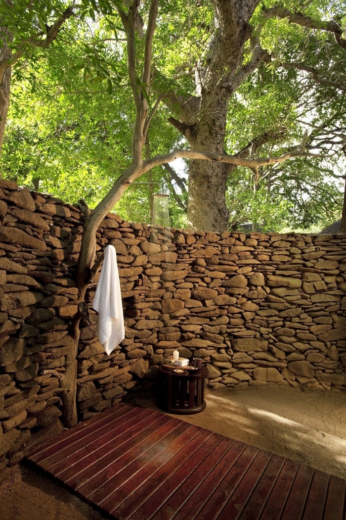 comment décorer un jardin de style zen aux murs en pierre avec terrasse en bois et sable, douche de jardin pluie