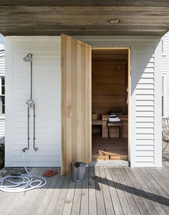 modèle de salle de bain extérieure aménagée sur une terrasse en bois avec toiture bois et douche exterieur en métal