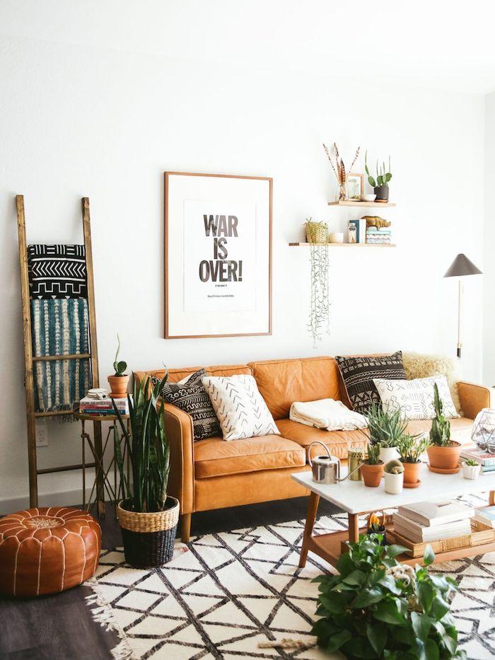Cadre sur le mur avec signature la guerre est finie, echelle de rangement en bois, canapé orange et pouf, plantes vertes