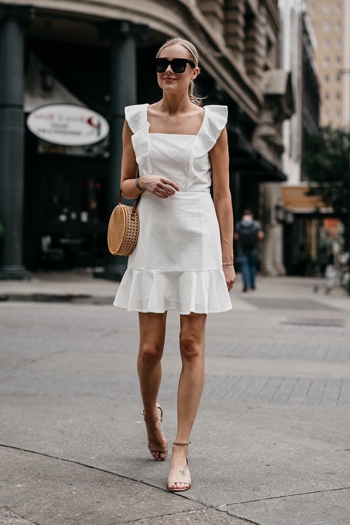 style vestimentaire femme élégante avec robe courte blanche à détails volants, modèle de sac à main tendance paille