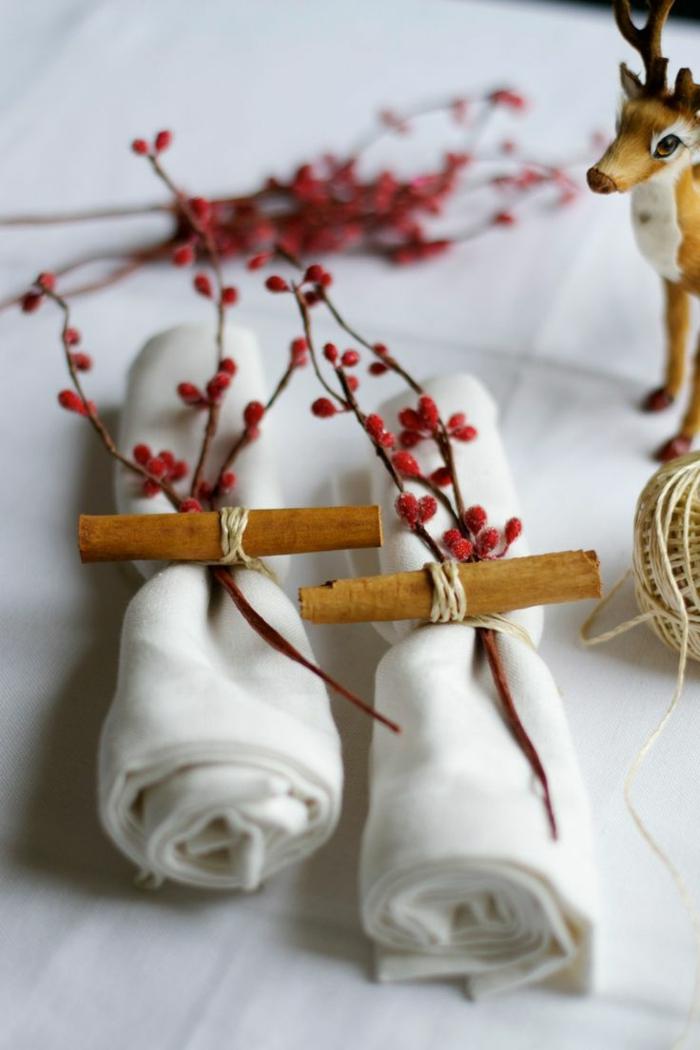 serviettes blanches attachées de manière originale, branches avec baies rouges, cerf décoratif