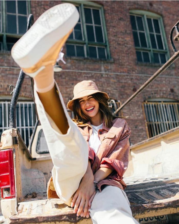 chapeau bucket beige, sneakers dorés plateforme blanche, t-shirt blanc, chemise rose, pantalon blanc