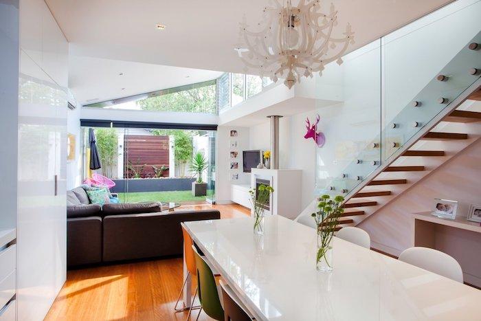 cuisine blanche ouverte sur salon avec cheminée blanche et canapé gris d angle sous extension à toit en pente, ouverture sur salle à manger moderne