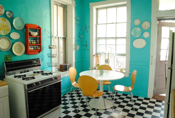 Bleu cuisine rétro avec carrelage de sol en carré, four vintage cuisinière, jaunes chaises et table à manger ronde
