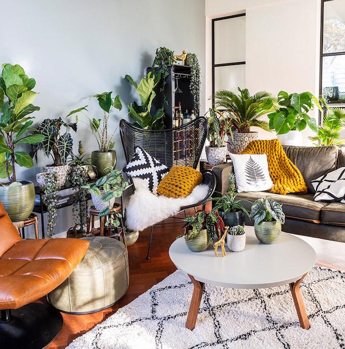 table ronde basse avec de petits pots de fleurs, fauteuil cuir marron, canapé gris, plaid jaune moutarde, accents exotiques, pouf gris et végétation luxuriante