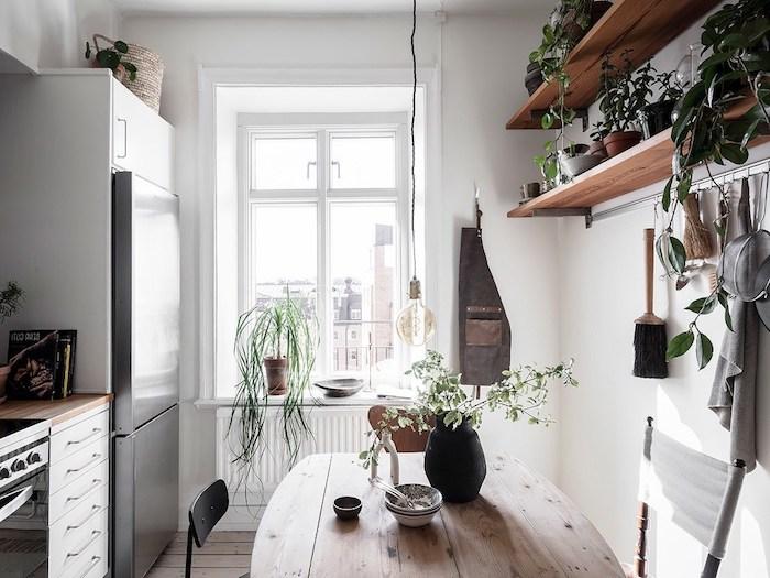 etageres bois surchargées de petits pots de fleurs, table cuisine bois brut, meuble cuisine blanc à plan de travail bois, suspension ampoule originale
