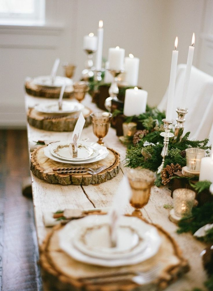 table rustique en bois, sous assiettes rondins de bois, bougeoirs raffinés, branches vertes