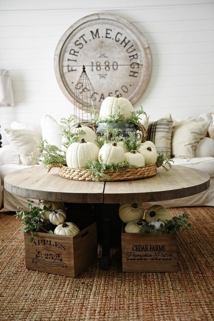 table ronde en bobine de bois, paniers rustiques, mini citrouilles blanches, sofa avec coussins, parement mur en planches