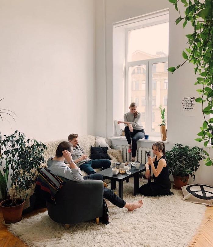deco salon scandinave à touches bohemes, tapis moelleux, table basse noire, murs blancs et plantes vertes en pot