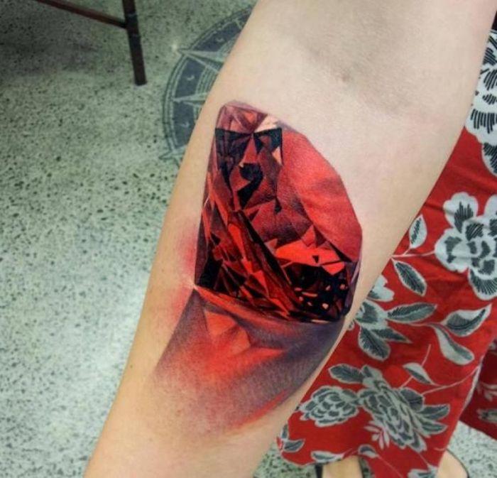 tatouage rubis, image de rubis rouge aux facettes, réflexion, tatouage femme en rouge et noir
