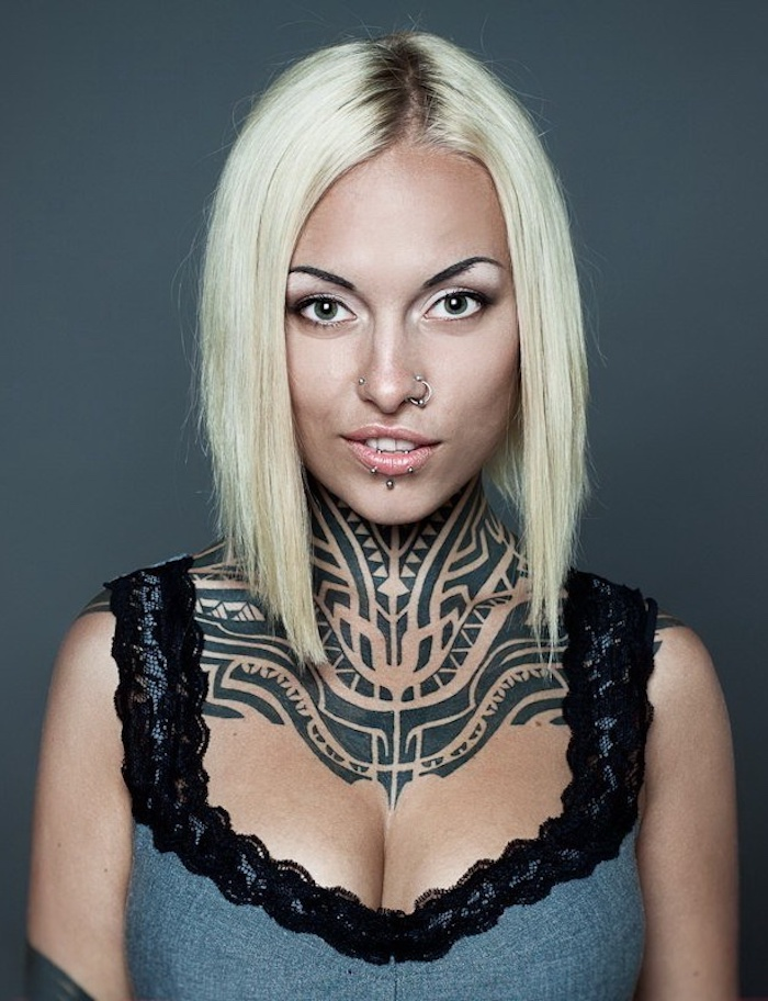 tatouage tribal cou, motifs ethniques encre noire, femme blonde, piercing nez et lèvres, débardeur dentelle