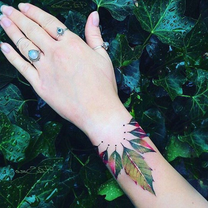 feuilles aquarelles plusieurs couleurs, tatouage au dessus du poignet, bagues pierres bleues, feuillage vert