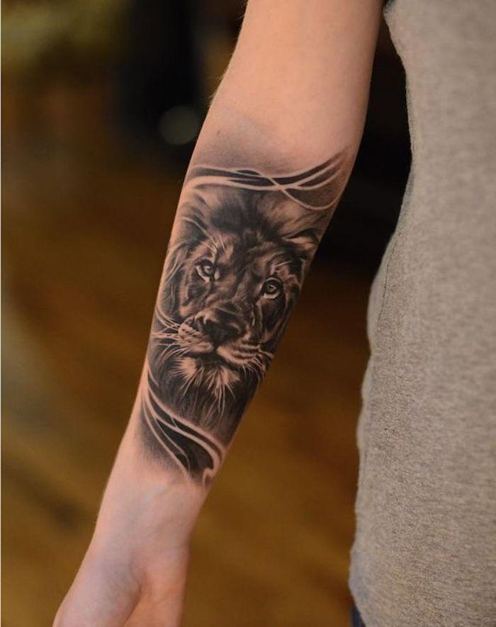 image de lion tatouée avant-bras, vêtement gris, tatouage monochrome femme