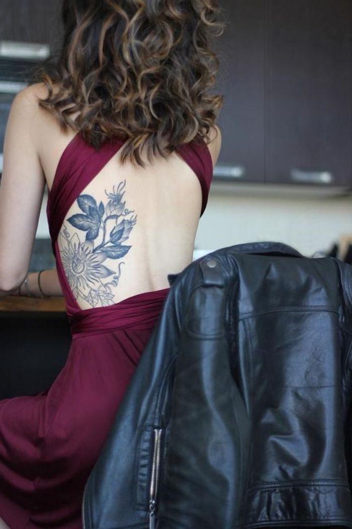 tatouage dos femme aux motifs floraux, robe bordeaux, cheveux bouclés, tatouage cote noir