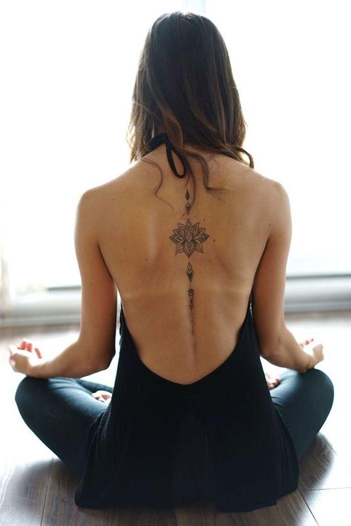tatouage lotus symbolique, femme qui médite, tatouage dos minimaliste, combinaison noir