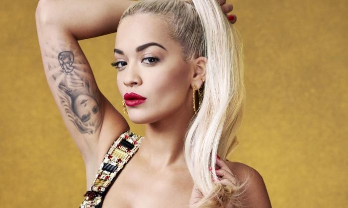 Rita Ora aux cheveux longs de couleur blond blanc avec racines châtain foncé attachés, maquillage avec rouge à lèvre rouge mate
