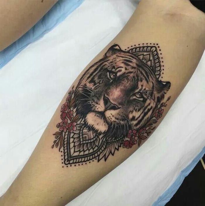 tatouage lion et fleurs au mollet, animal totem, tatouage symbolisant la force et le courage