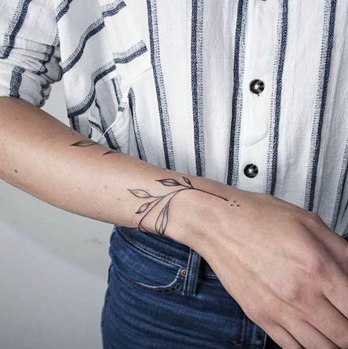 chemise rayée, jeans bleus, tatouage discret motifs végétaux, tatouage femme main