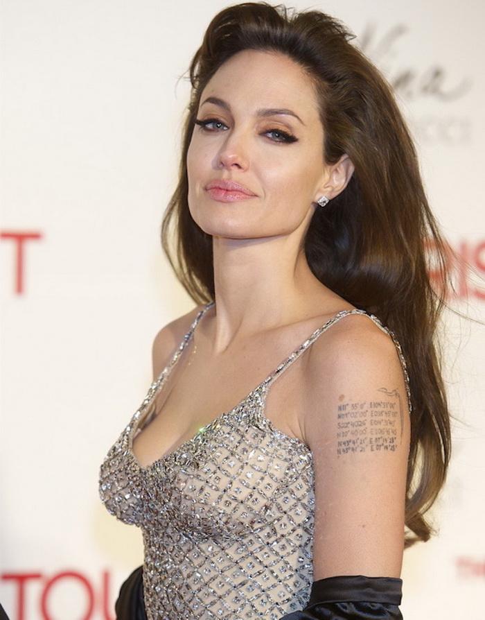 Anjelina Jolie, tatouage script sous l épaule, robe nude aux éléments gris métallique, eyeliner noir