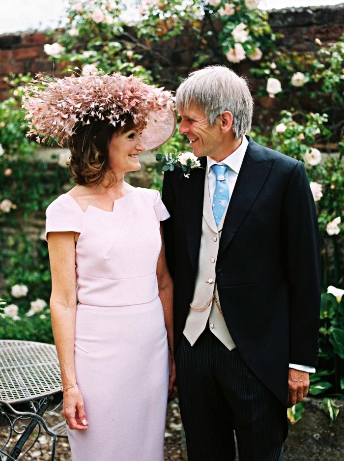 idée de tenue mariage femme 60 ans pour la mère de la mariée, robe rose à coupe droite et à manche courte avec encolure asymétrique, accompagnée d'un chapeau de mariage de la même couleur