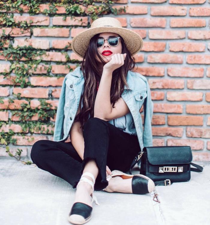 pantalon noir, veste denim, chapeau en paille, lunettes de soleil, mur en briques, plantes grimpantes, espadrilles bimatières
