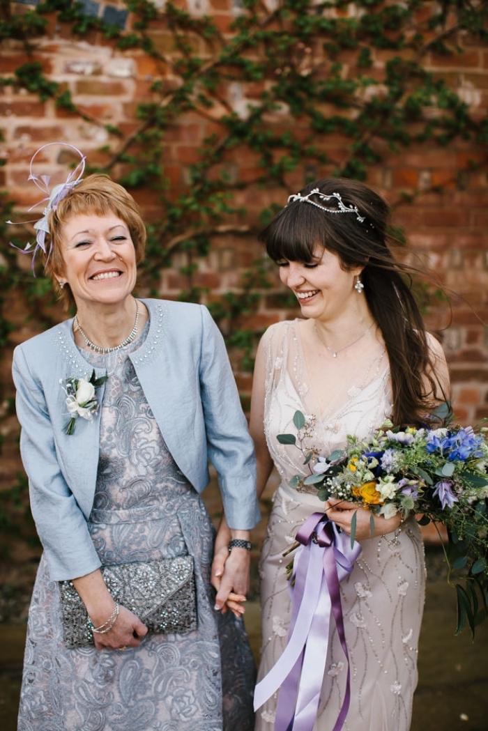 ensemble pour mère de la mariée, robe de cocktail bleu-gris et sa veste courte bleu clair assortie accompagnés d'une pochette à sequins