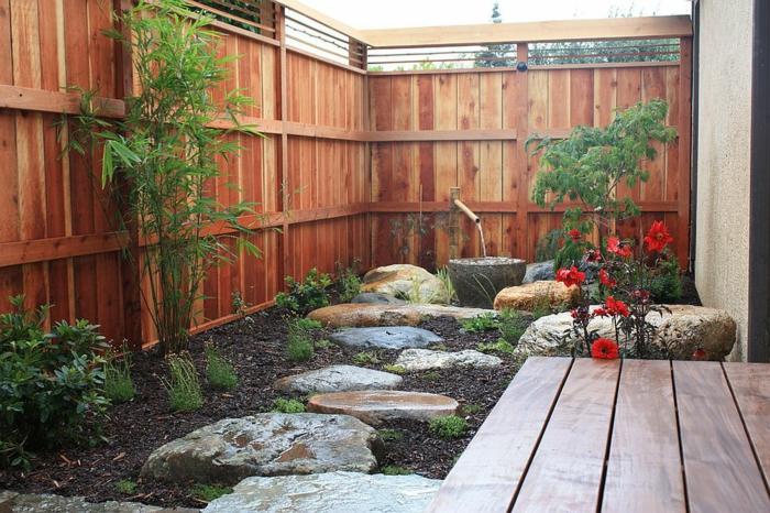 aménager un petit jardin, grandes pierres posées dans un parterre, terrasse en bois, fleurs et arbrisseaux