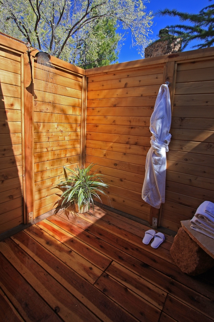 aménagement petite salle d'eau dans la cour arrière avec sol et murs en bois marron, douche fixe extérieure en métal