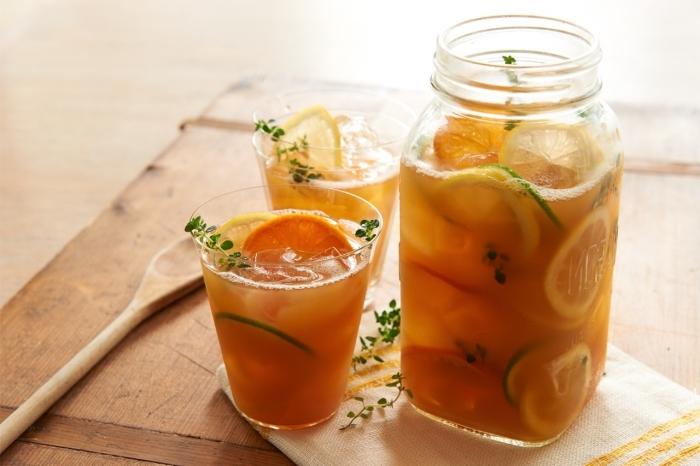dans quel contenant préparer un thé glacé, bocal rempli de thé vert refroidi avec tranches de citron vert et glaçons