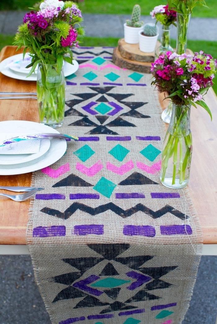 chemin de table en tissu de lin décoré de motifs géométriques, bouteilles en verre, rondins de bois, pots de fleurs avec succulentes