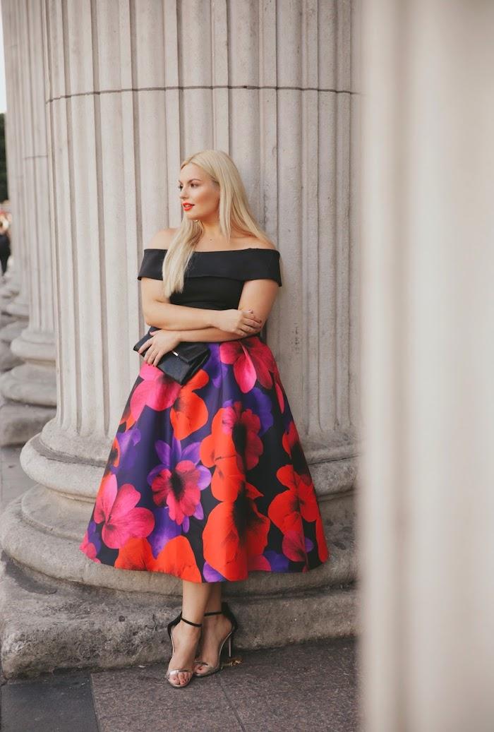 modele de robe de ceremonie grande taille femme blonde, robe à top noir à bretelles tombantes et jupe longue évasée à imprimé fleuri