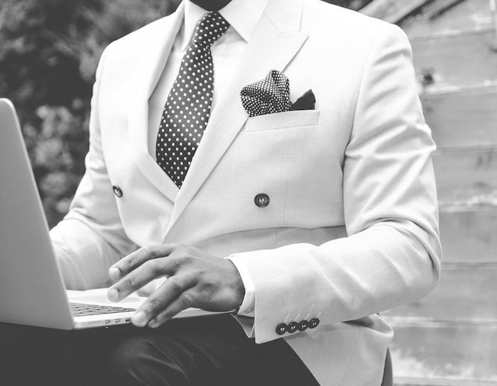 tenue chic homme en costume avec un veston blanc, chemise blanche et cravate noire à pois, pantalon noir