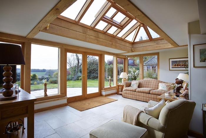 architecture traditionnelle de veranda à ossature bois et vitres, carrelage beton, canapé à carreaux traditionnel, meuble bois et fauteuil gris