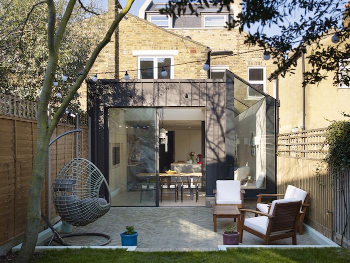 surface habitable maison dans veranda grise à vitres pour cuisine grise et blanche ouverte sur salle à manger contemporaine, ouverture sur salon de jardin bois avec balancelle exterieure