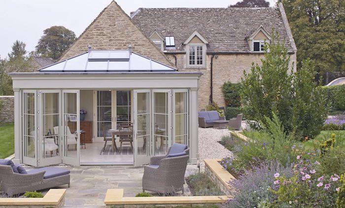 idee de veranda exterieure séparée d une maison traditionnelle, extension séparée aménagée en salon salle à manger dans un jardin avec salon de jardin en rotin autour