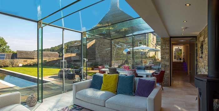 salle a manger salon sur extension vitrée avec canapé gris à coussins colorés et salle à manger avec table blanche et chaises colorées