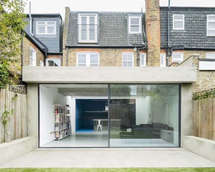 extension beton originale a amenagement minimaliste en cuisine avec bar ouverte sur salon doté de bibliotheque blanche et canapé d angle gris